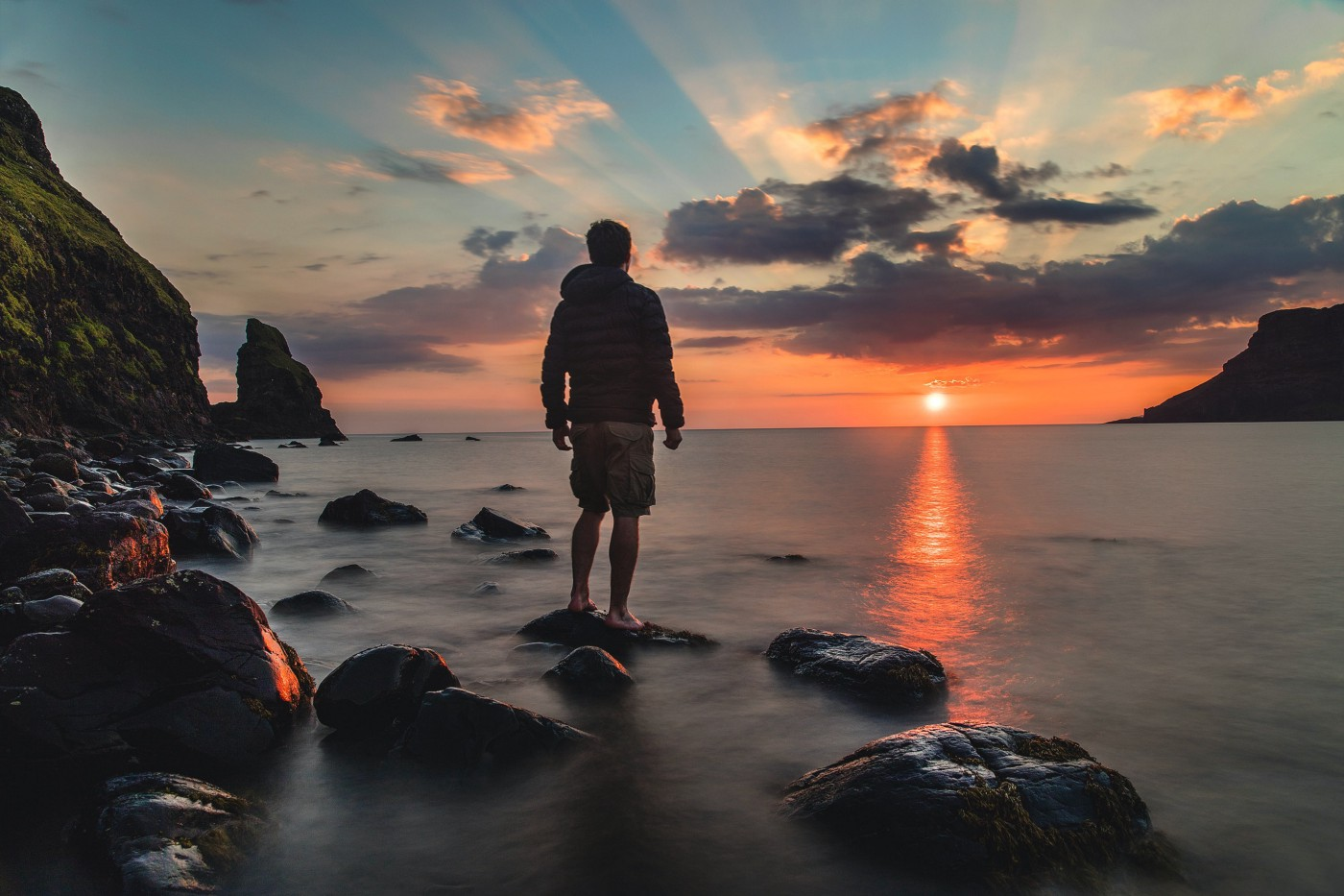 Man standing on rocks in the water looking out at the sunset above the ocean.