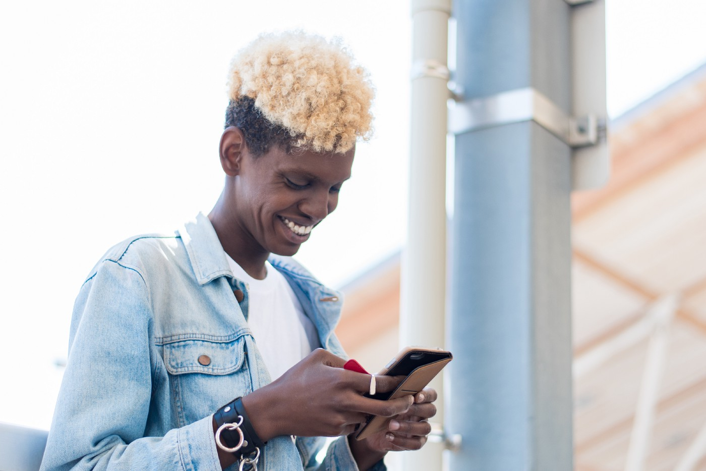 A side view of a non-binary African American person using their smartphone.