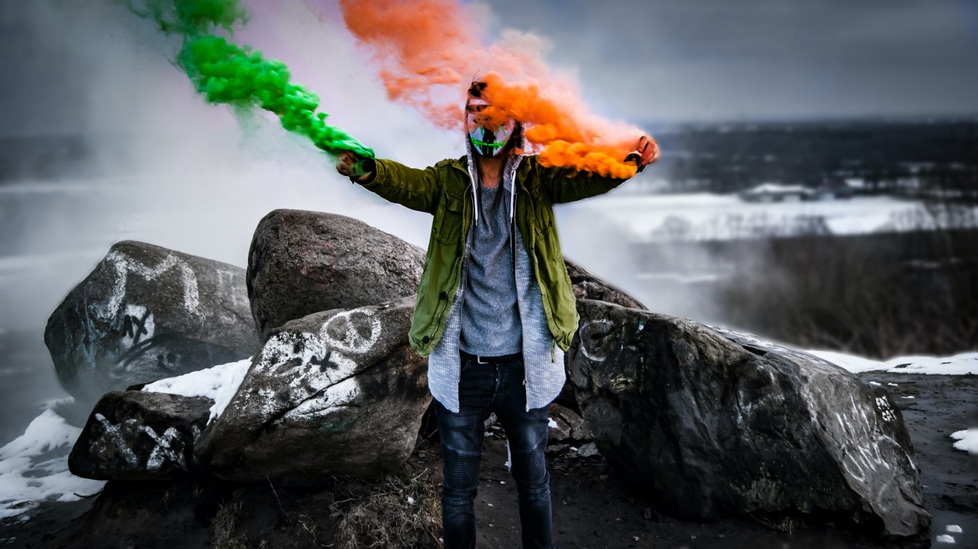 A man holding green and orange flares