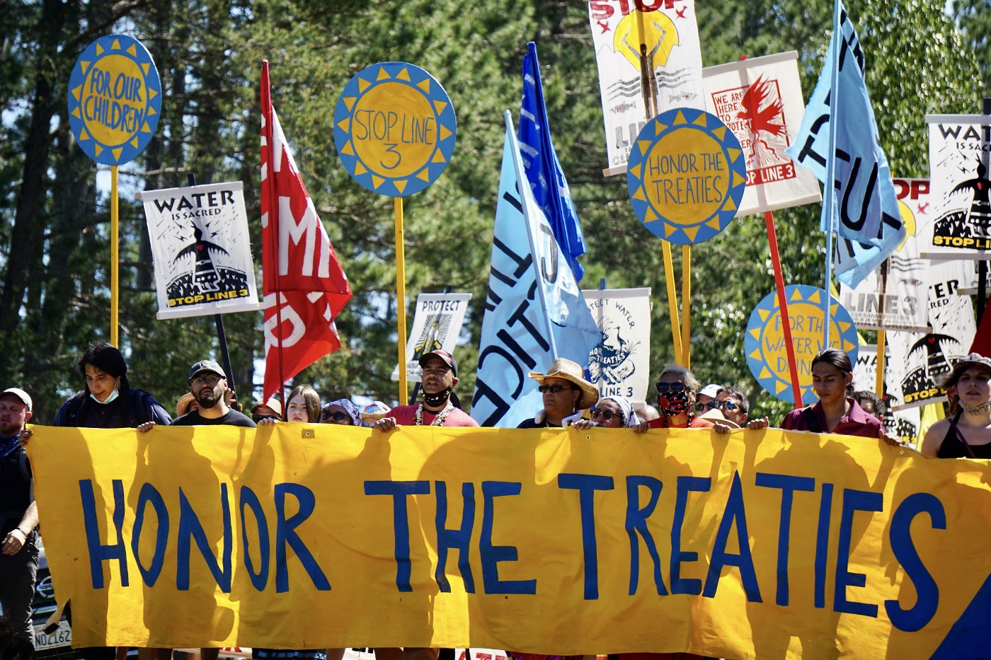 """People stand behind a banner reading """"Honor the Treaties"""" at a protest against Line 3."""