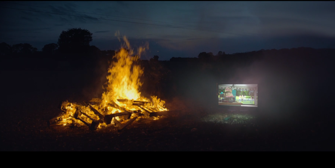 A bonfire burns at night, with a TV glowing beside it. A still from the 'our stories' TV ad by Uncommon Studios.