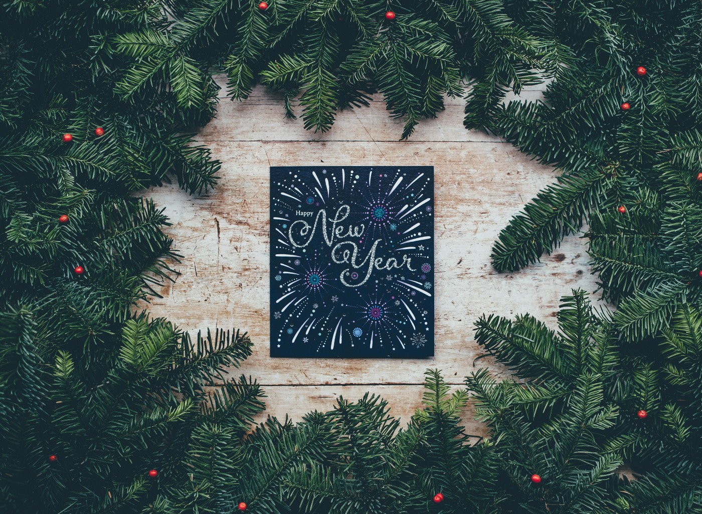 Photo of pine wreath around a greeting card that says New Year