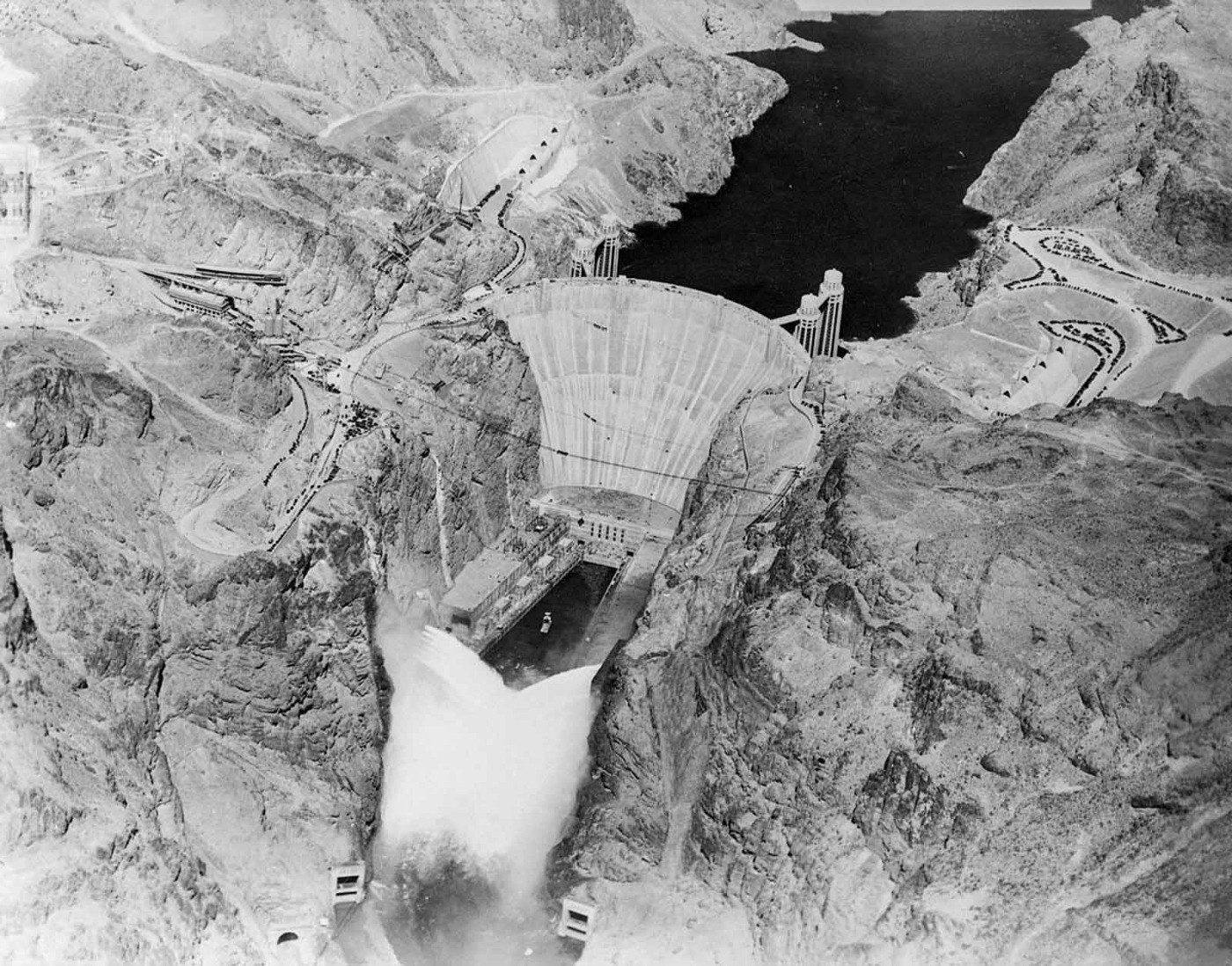 An antique photo of the Hoover Dam just after completion, with the water level visibly higher than in the previous photo.