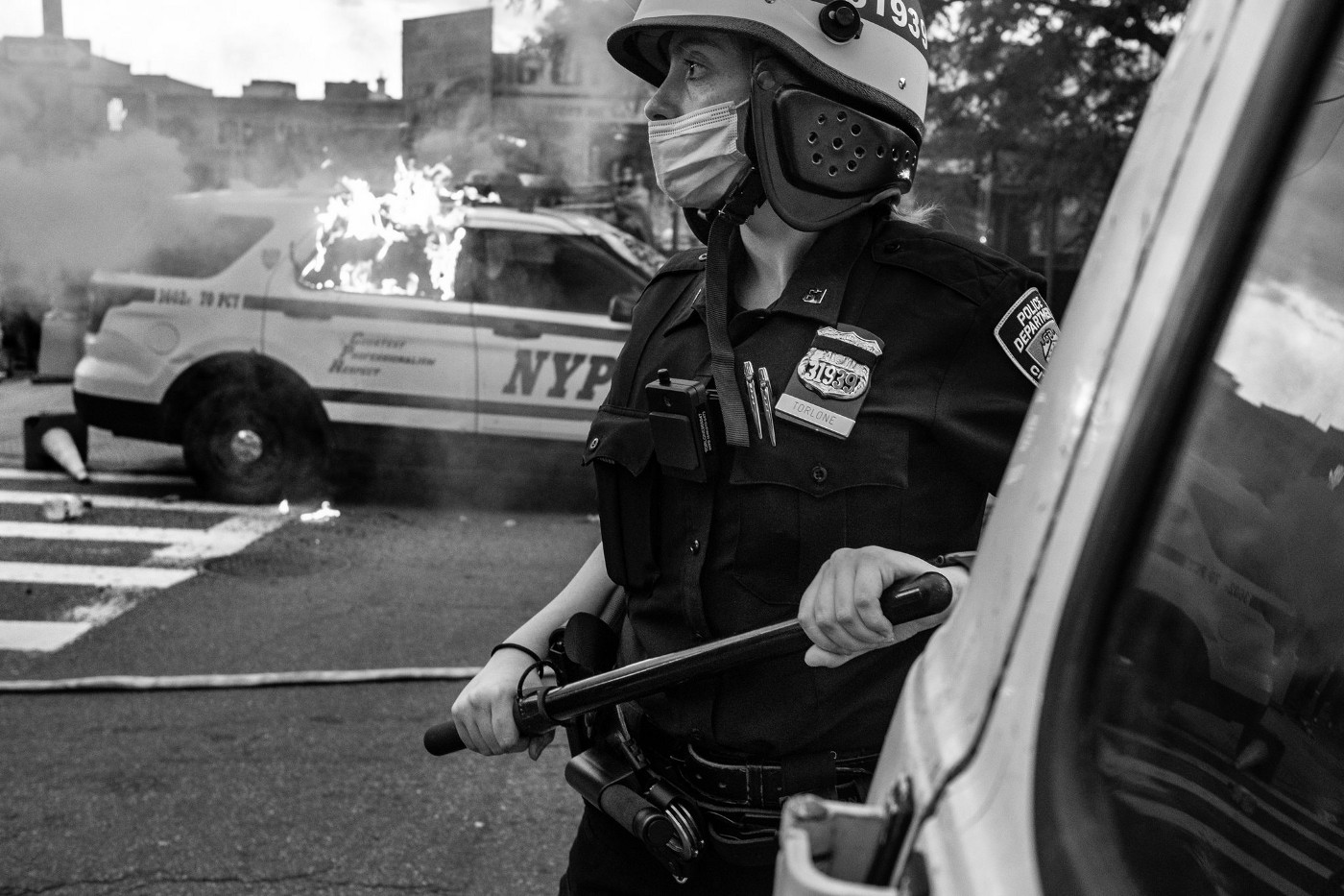 NYPD Officer with nightstick in front of a burning police vehicle.