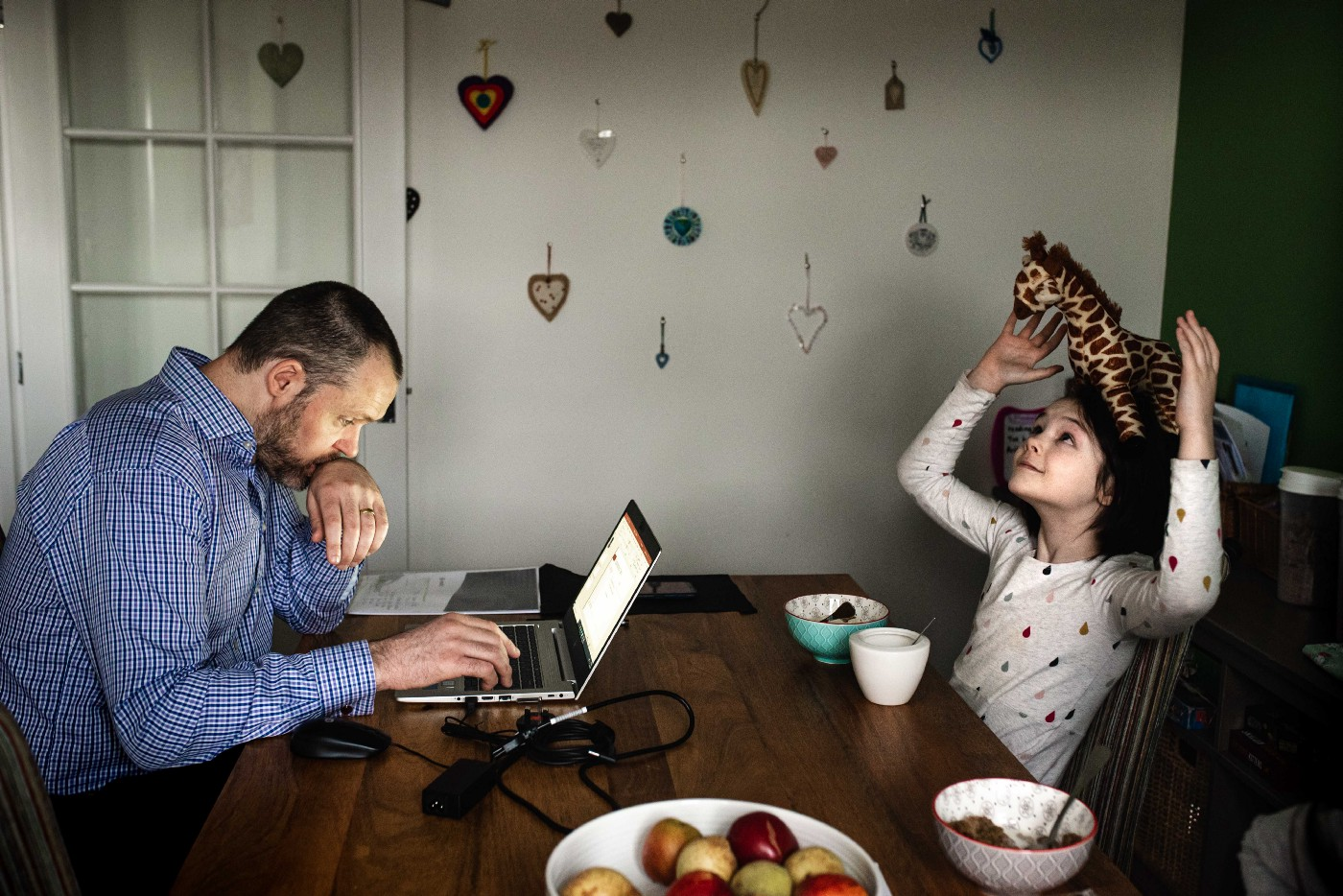 a man sits at a laptop working whilst opposite a girl puts a toy giraffe on her head