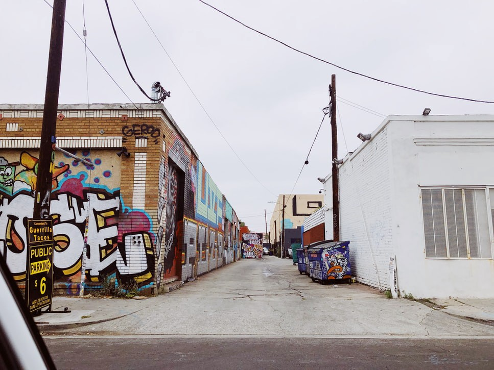 lateral view of Mateo Street in Los Angeles, gray sky, graffiti-covered buildings and dumpster