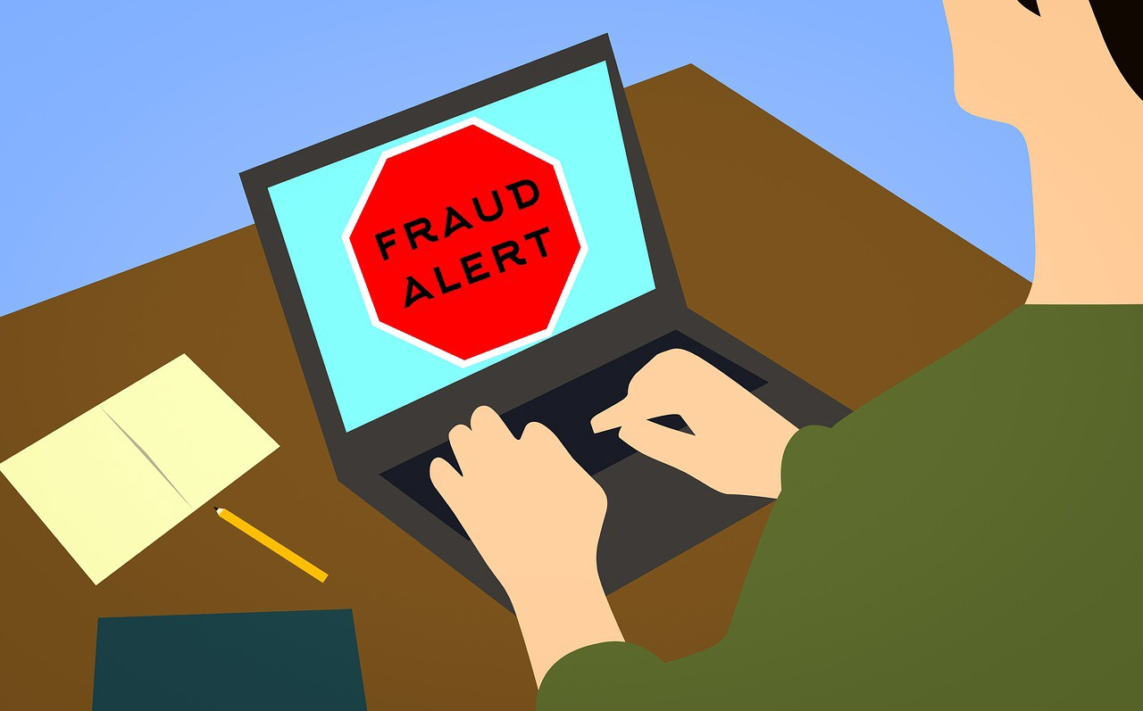 """An image of a person at a laptop with the message """" Fraud Alert"""" showing on the screen."""