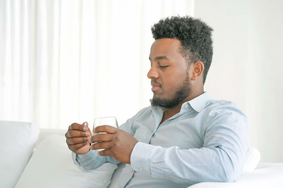 Person in light blue shirt sits on a white sofa with a clear water glass in one hand and blue pill in another.