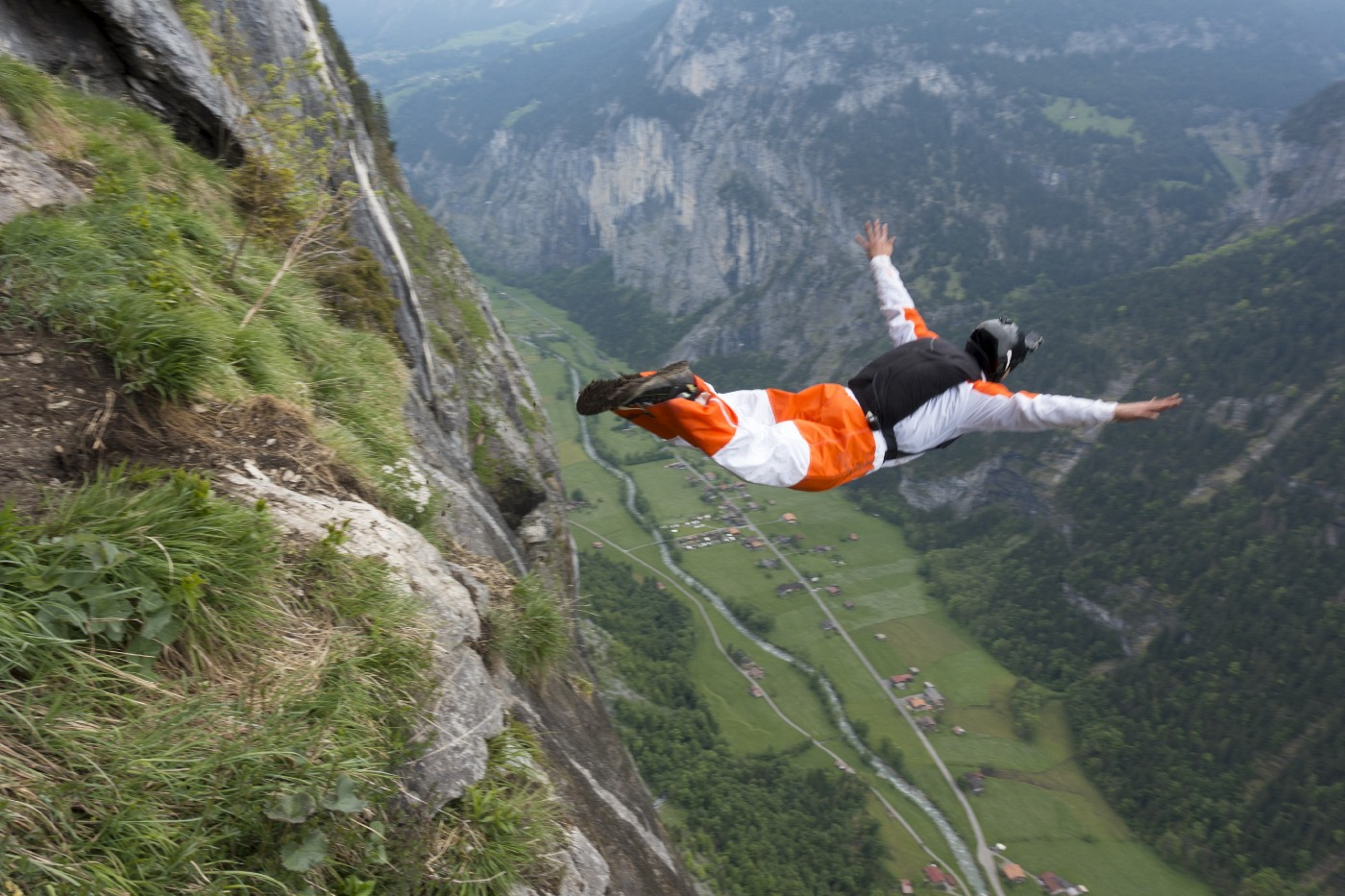Base jumper diving  down into a valley.
