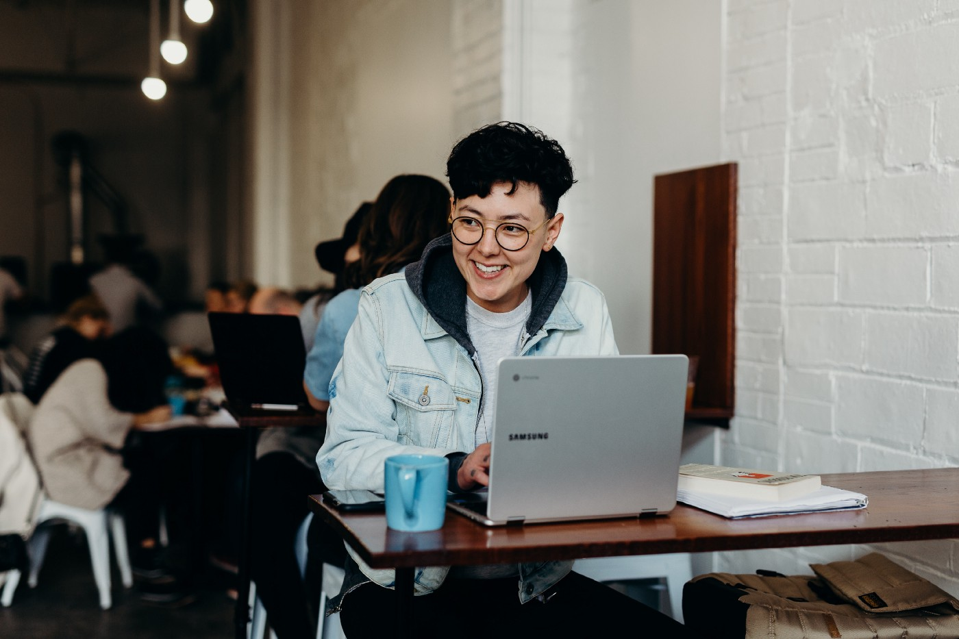 Woman sitting in front of an open laptop in a café, smiling