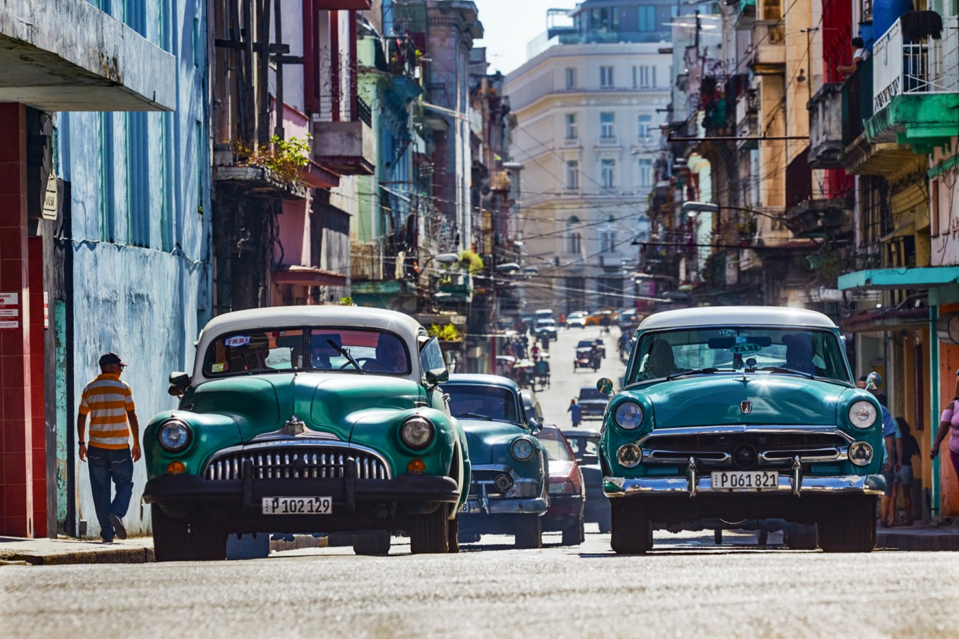 2 Vintage  cars. 1 turquoise with white roof, other light green with white roof in sunlit centre of busy Havana, Cuba.