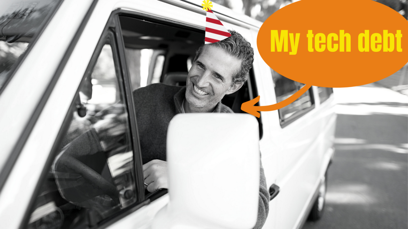 """image captioned """"my tech debt"""" showing a smiling man in a car wearing a party hat"""