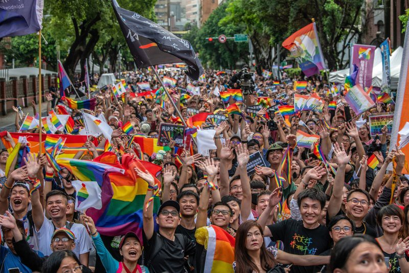 Demonstrators waving rainbow flags and smiling