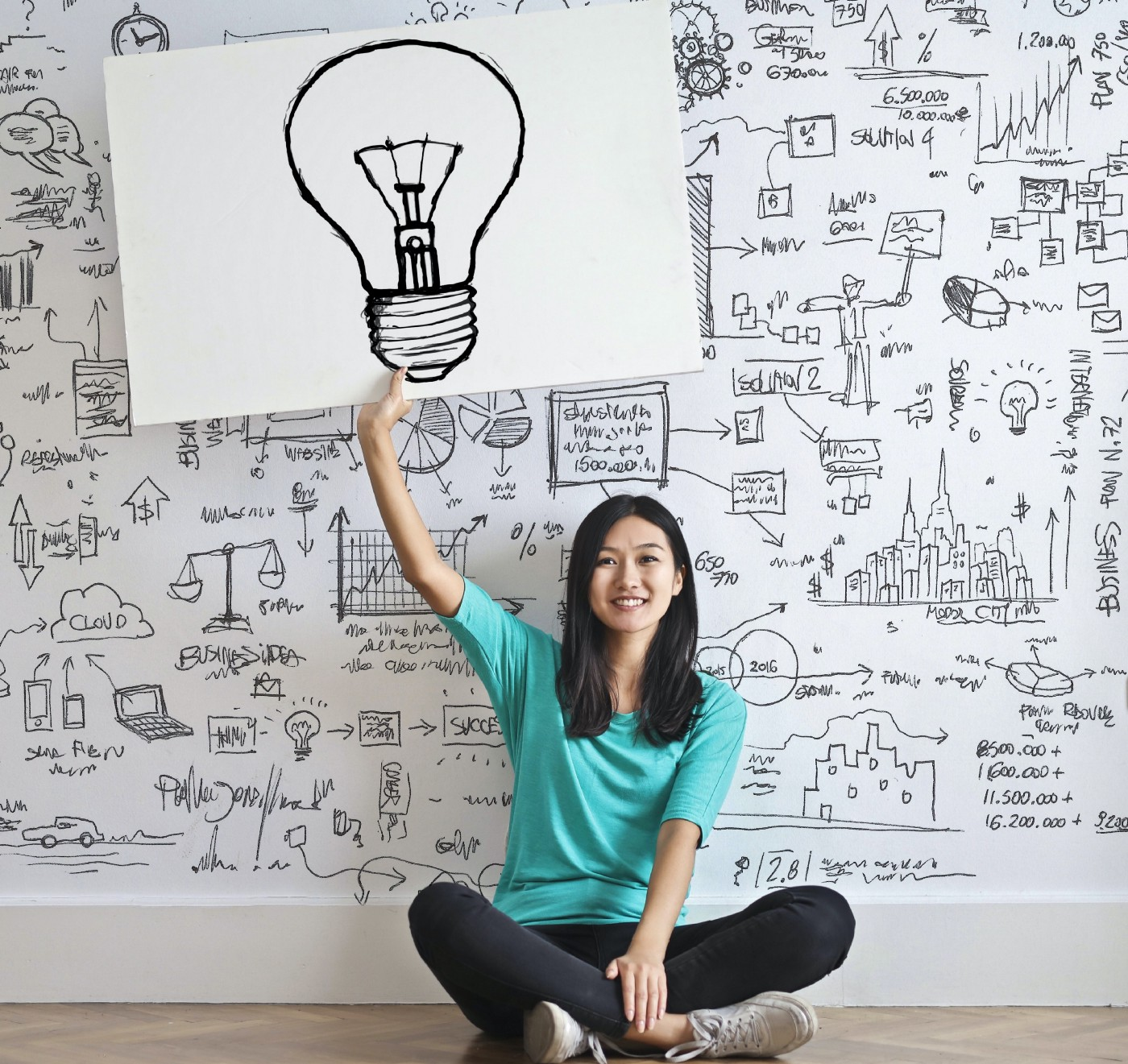 A girl sits on the floor smiling and holding up a sign with a light bulb. Behind her is a wall with numerous sketches, diagrams, and ideas.