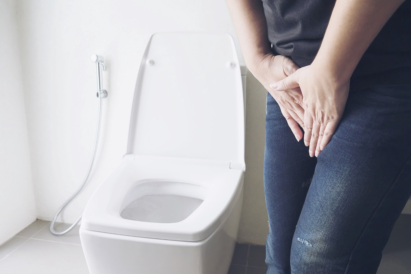 Woman holding her pelvic area by a toilet.