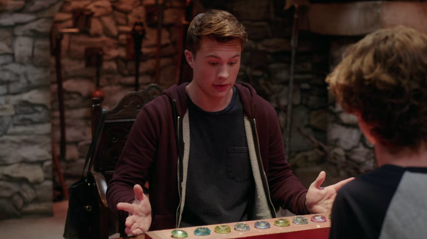A white teen boy looks at a row of gemstones nestled into holes on a wooden plank, on a table in front of him.