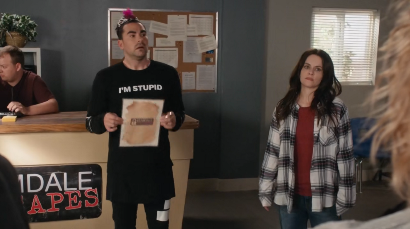 """Two people stand in an escape room lobby. The man is wearing an """"I'm the bride"""" crown and a shirt that says """"I'm stupid"""""""
