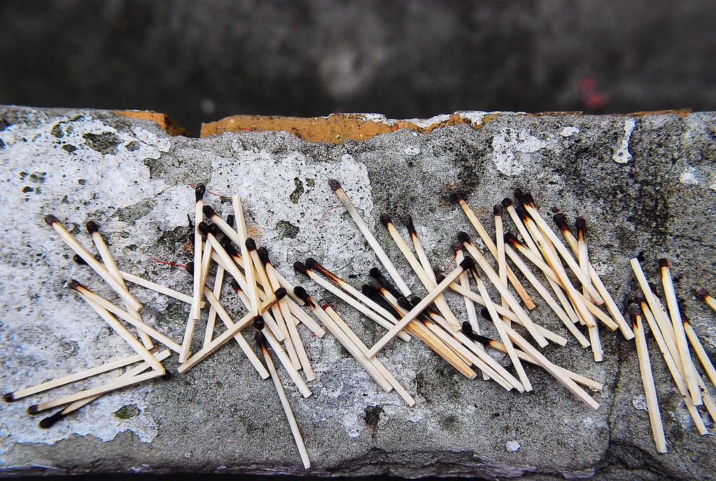 A pile of burnt-out matches on a piece of concrete.