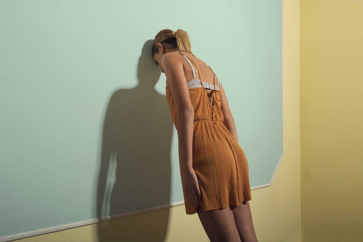 A woman in a corner leaning her head against a wall, as seen from behind.