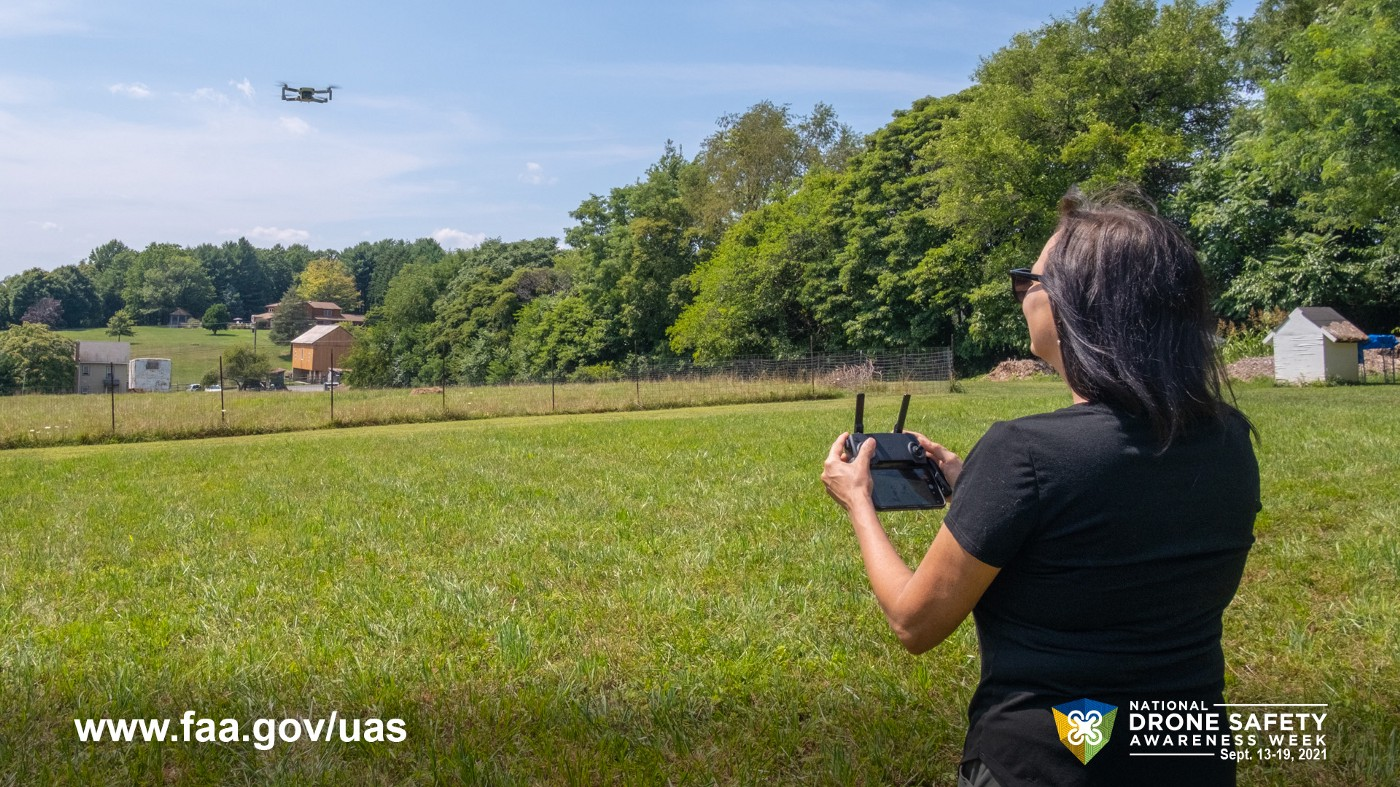 Woman flying drone over a field.
