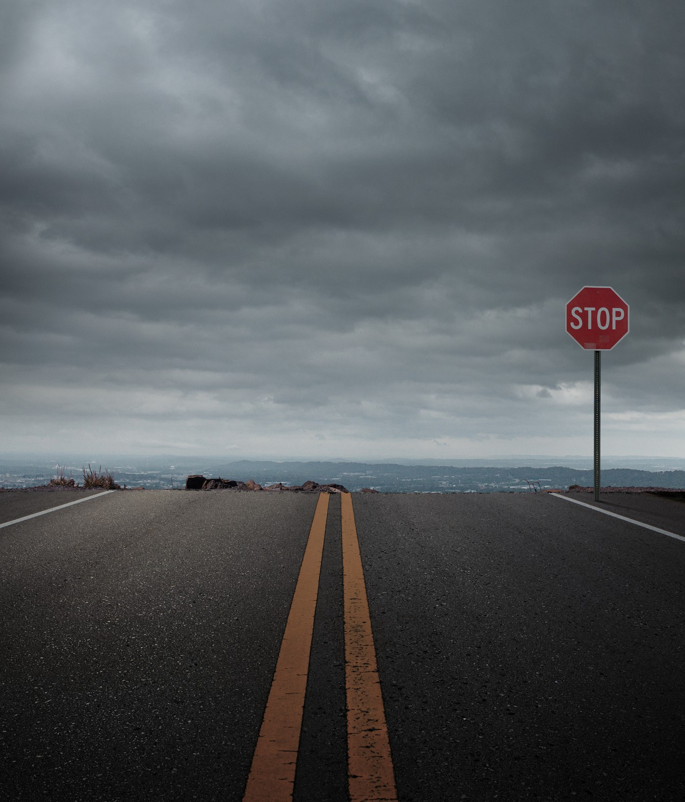 A road that leads off a cliff. A stop sign is right at the edge of the cliff, and the sky is gray and cloudy.