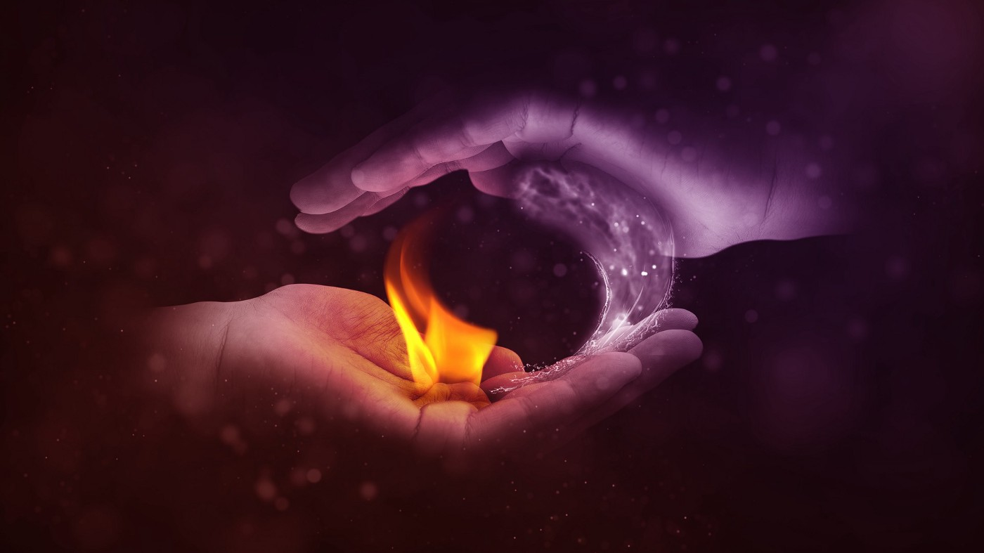 two hands making yin and yang with fire and water
