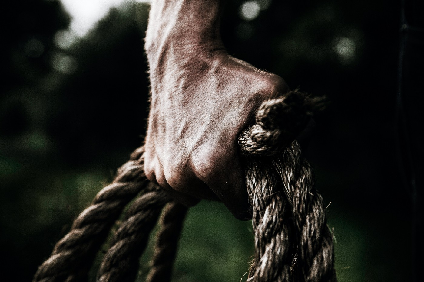 Tough man holding a rope in his hand.