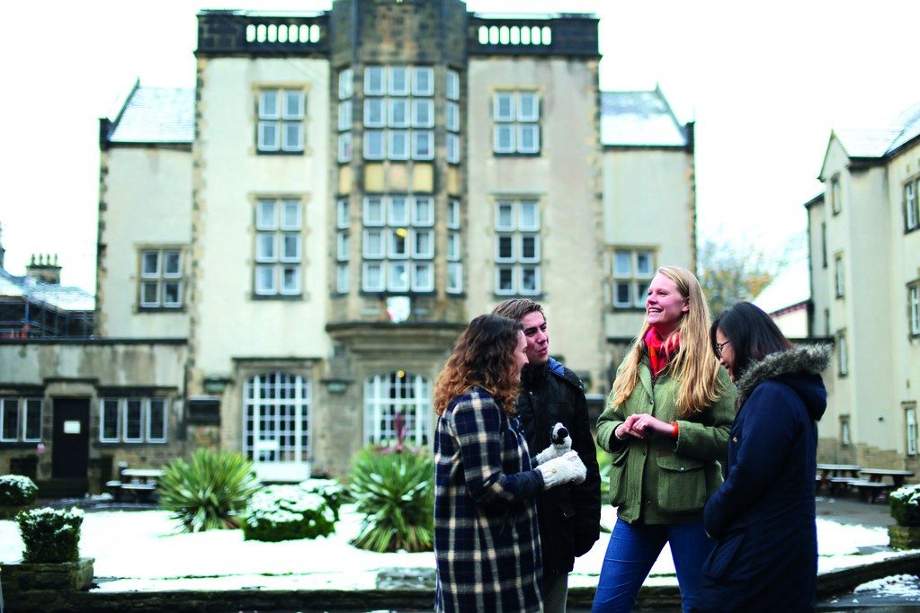 A group of students wrapped up in winter clothes stand chatting outside Devonshire Hall.