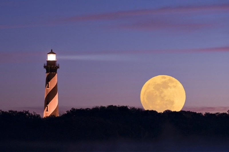 A black and white striped lighthouse at night, against a purple sky with a big yellow moon rising up next to it and its shining beam)