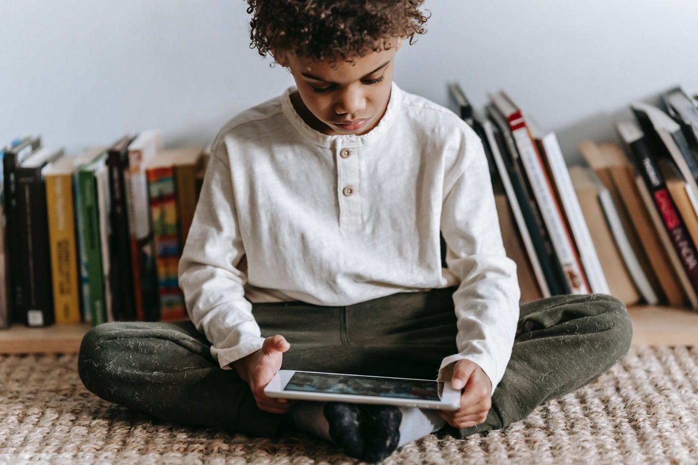Child sitting in front of a row of books reading on a tablet