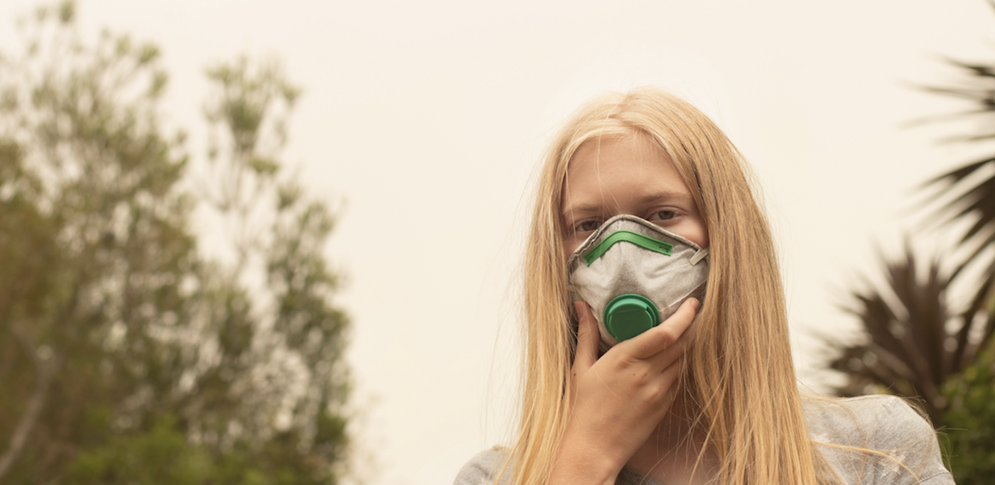 girl wears mask to protect herself from bushfire smoke