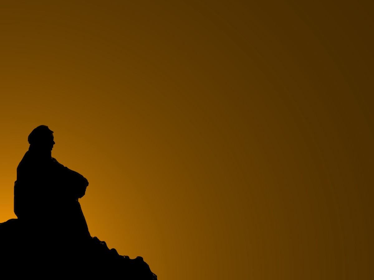 Photo showing the silhouette of a person sitting alone against a dark sky. It communicates a sense of sadness and isolation.