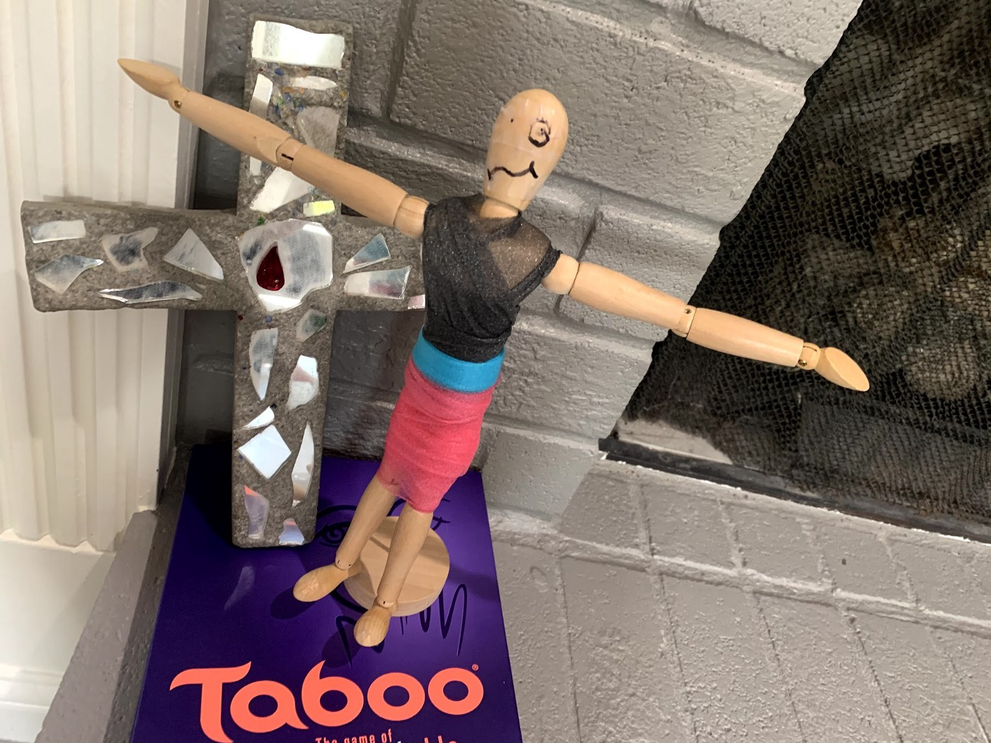 A mannequin stands on top of a game of Taboo with a cross behind her. She is holding her hands out, palms up, head tilted up.