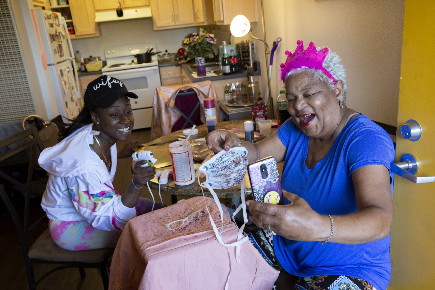 Curtisha Bell and her aunt Vicky Blake show progress of their festive surgical masks to friends and family on video chat.