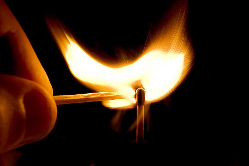 Closeup of a hand using a lit match to light another match.