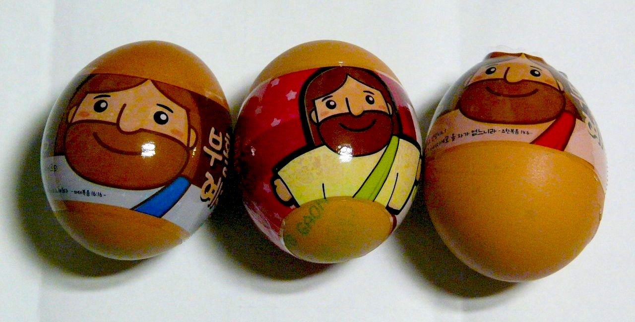 Three brown hen's eggs wrapped with plastic decals featuring cartoons of Jesus and writing in Korean