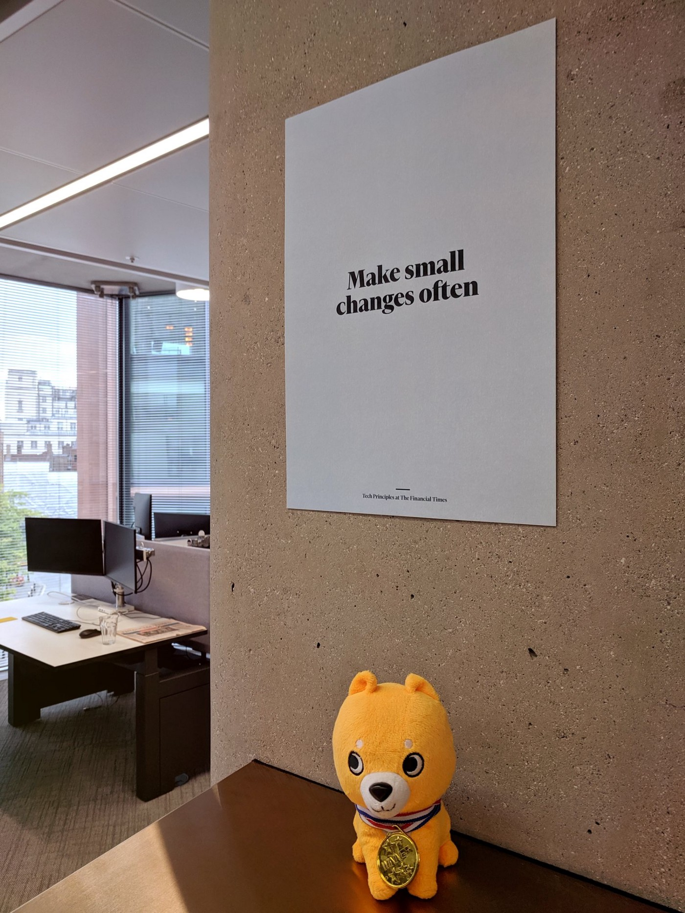 """A poster on the wall with the text """"Make small changes often"""""""