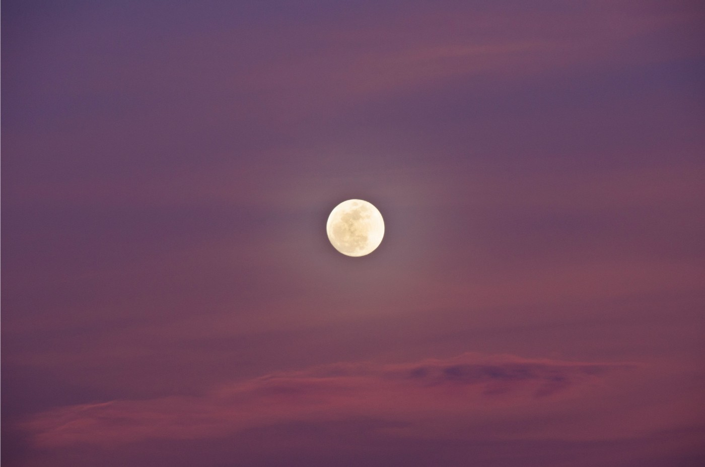 Full moon against pink-purple sky.