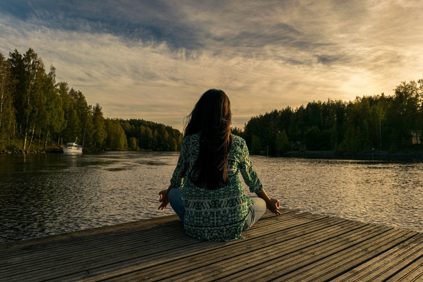 Woman sat meditating in front of scenic view