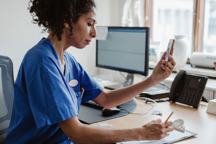 A photo of a nurse sitting at a desk. She is doing a telehealth appointment, holding up a phone using the video function- whilst taking notes on a clipboard.