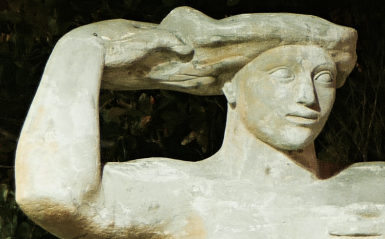 A close up view of the head and arms of a large statue. The statue's face is tranquil, and the lines are drawn as in Ancient Egyptian statues. With one arm the figure reaches up to touch her hair, which unfurls in a way which suggests the surface of the sea.