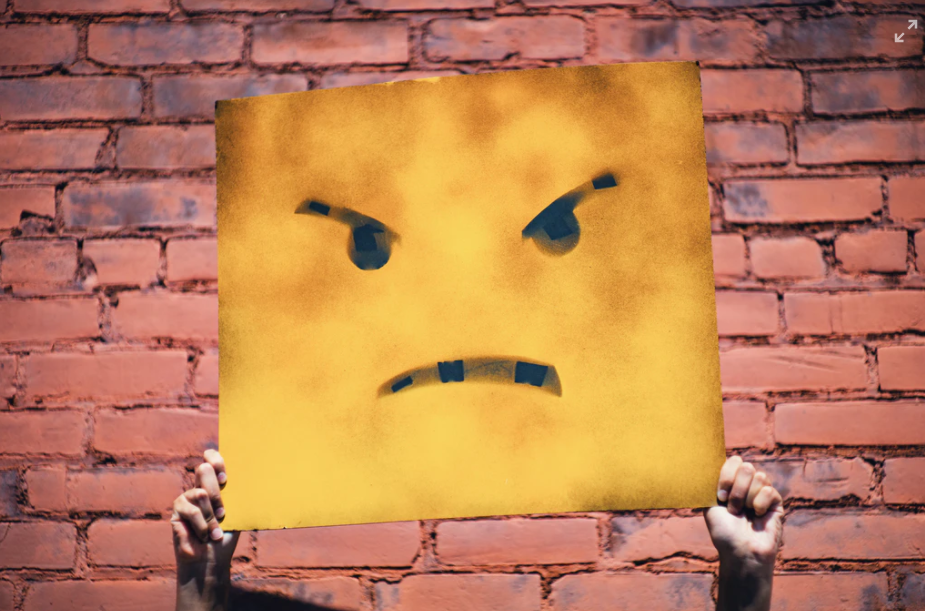 Hands holding up painting of frowning face