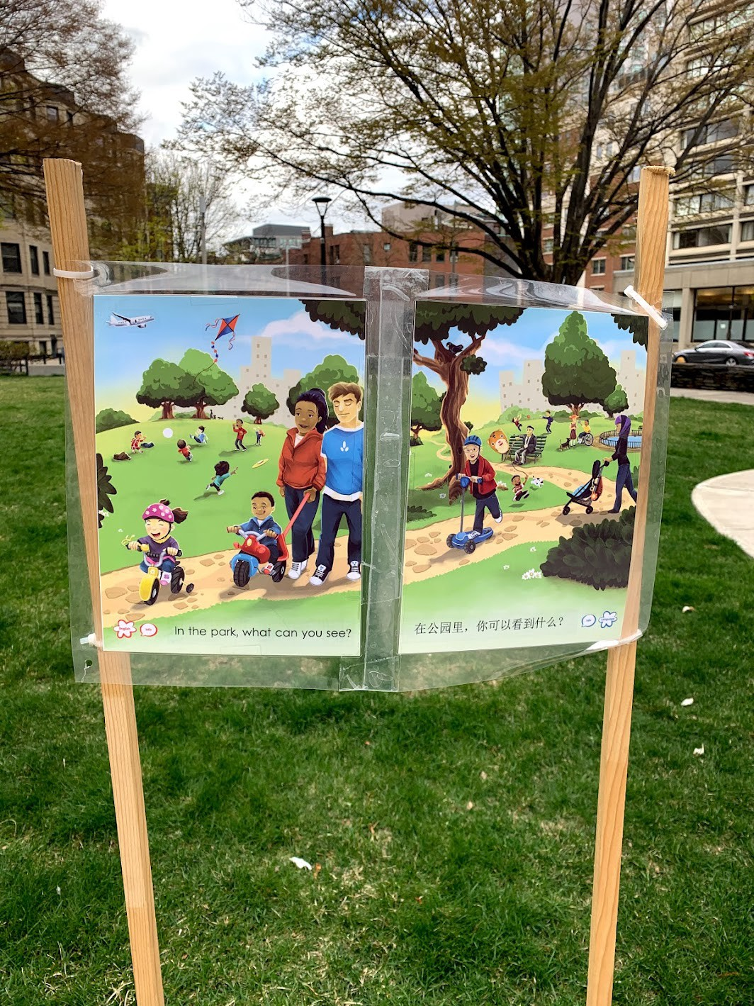 """A sign that reads, """"In the park, what can you see?"""" On the sign, There are images of people walking around and playing in the park."""