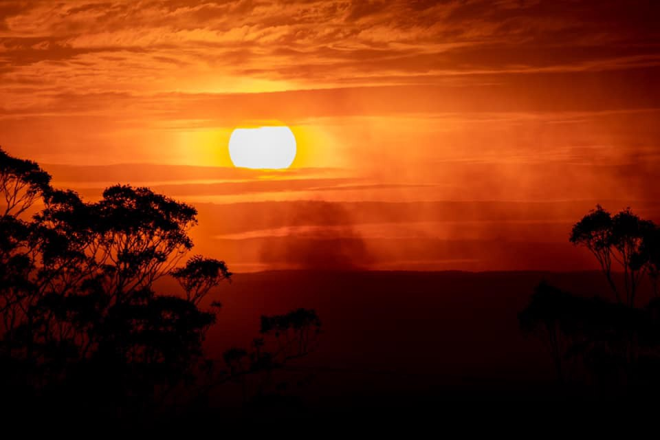 Photo of a setting sun, with a sky in deep oranges and yellows, with bushfire smoke visible in the foreground.