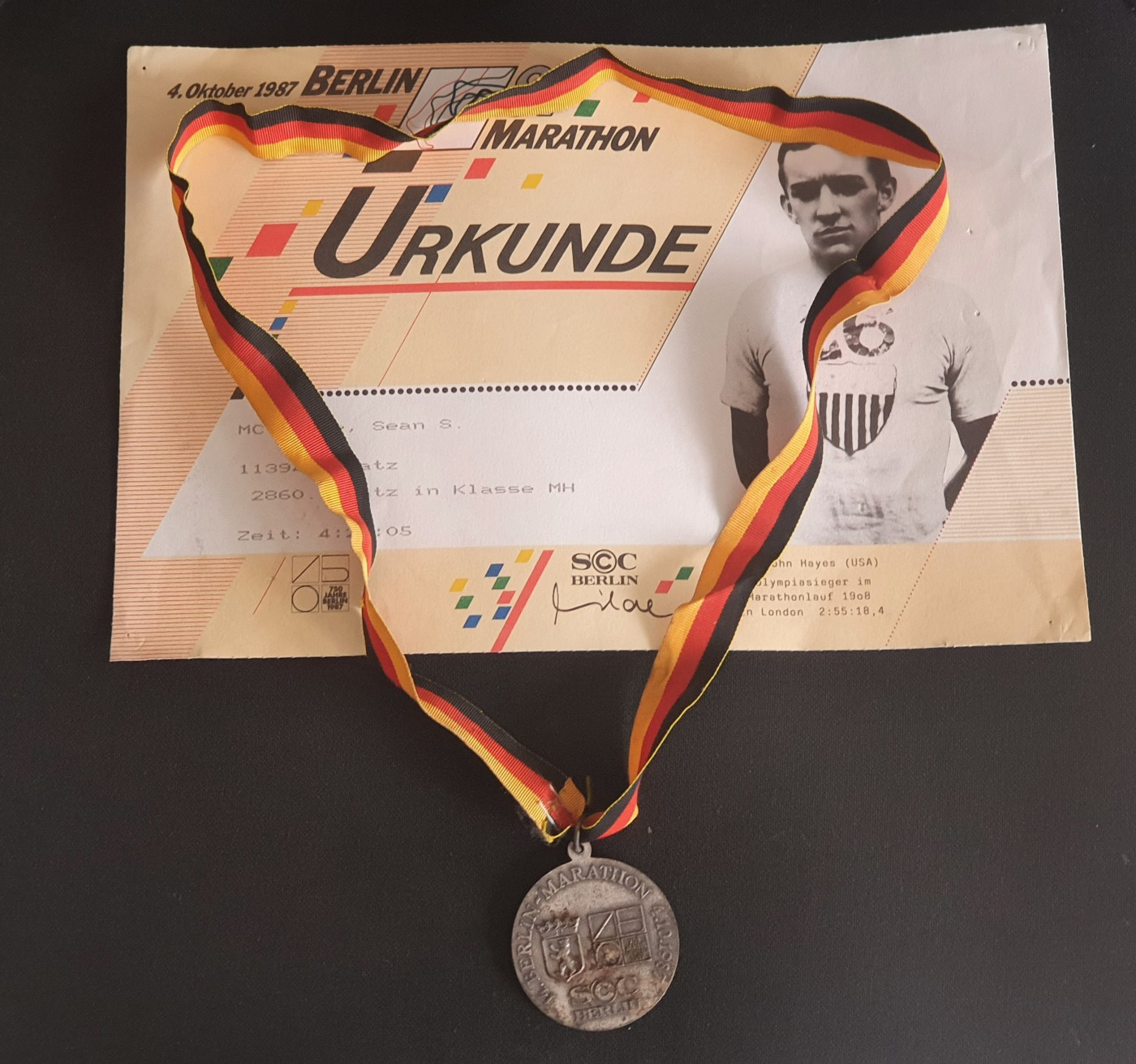 Berlin Marathon medal with the ribbon, depicting the colors of the German flag, sitting across the top of the Berlin Marathon Finisher's Certificate