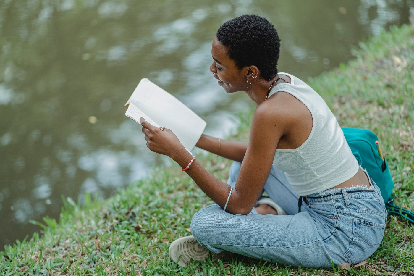Person reading a book by a lake.