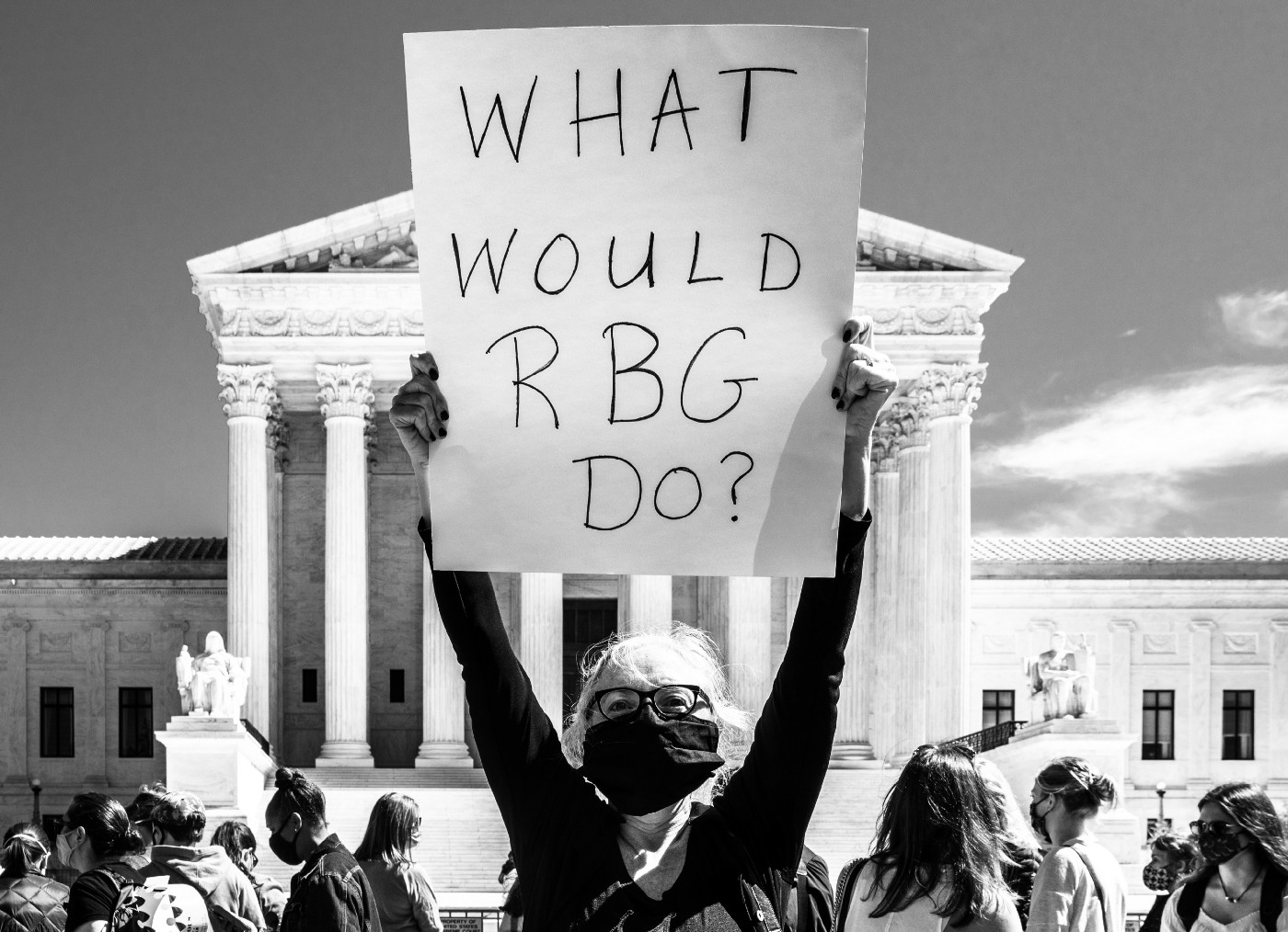 Masked woman outside the Supreme Court holding up a handmade poster showing What would RBG do?