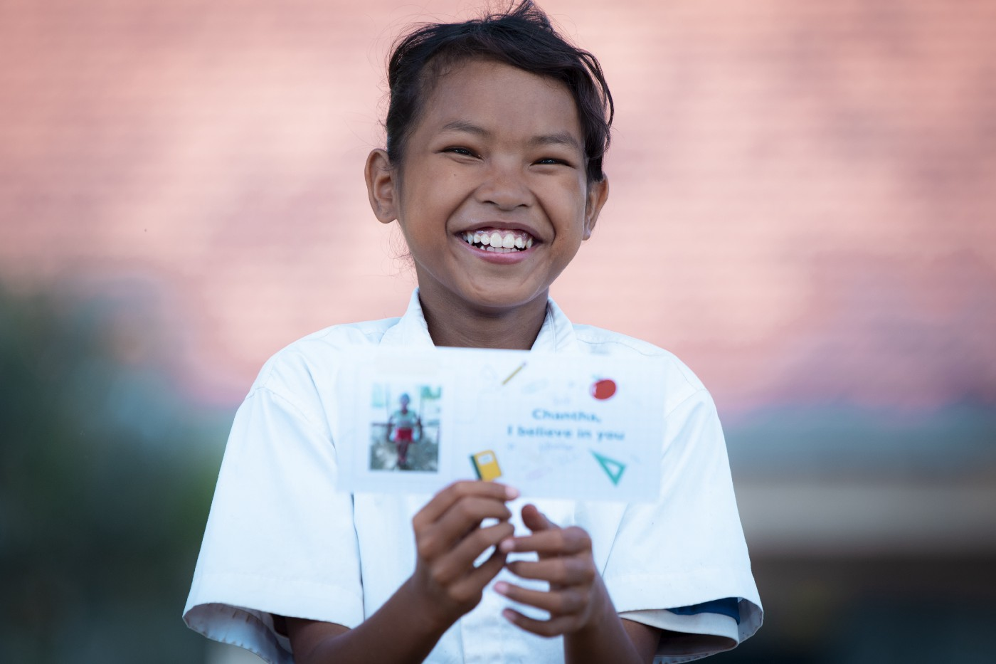 A young Asian girl smiles brightly into the camera. She is wearing a white button-down shirt holding up a small card.