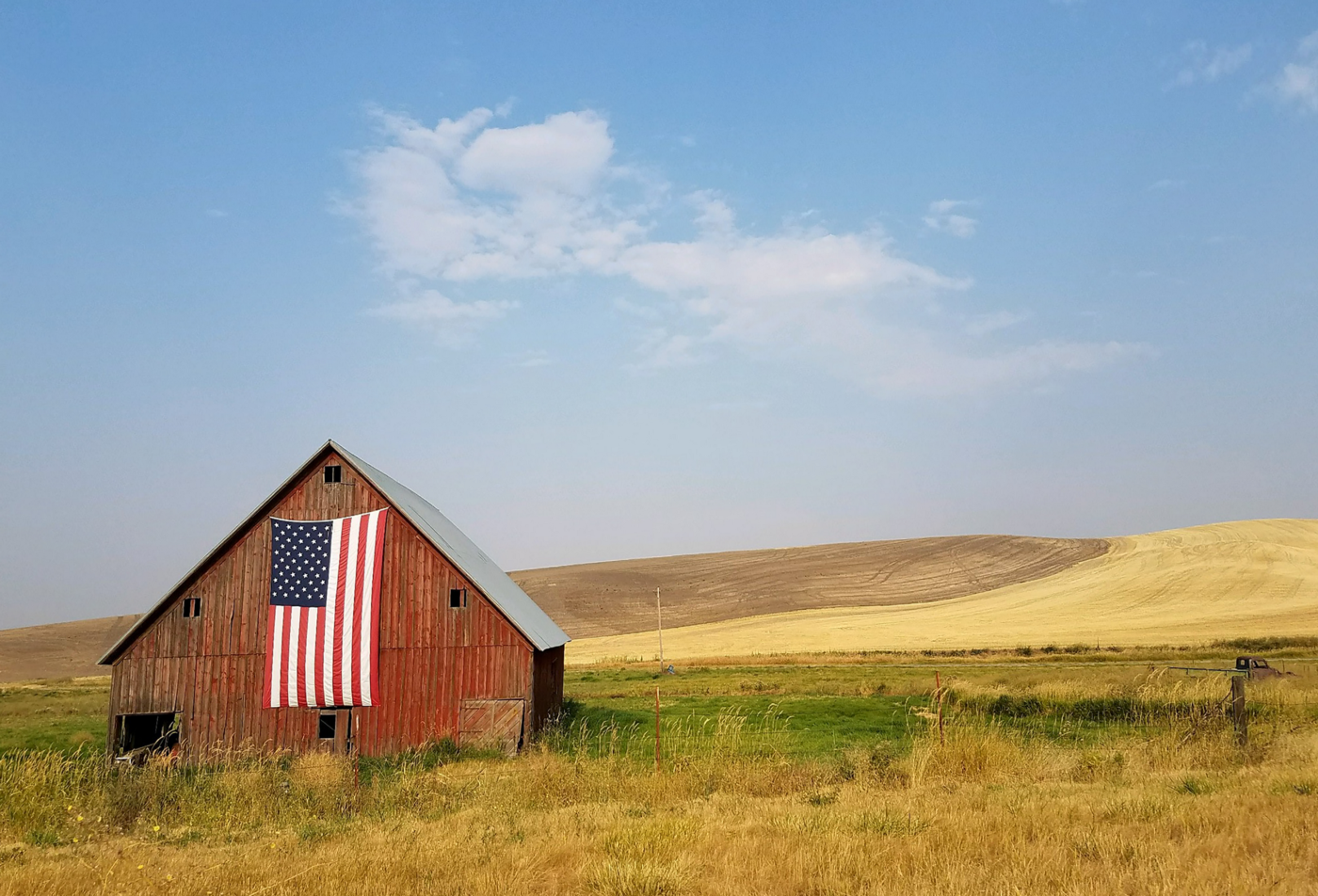 Red barn with American flag in an open field