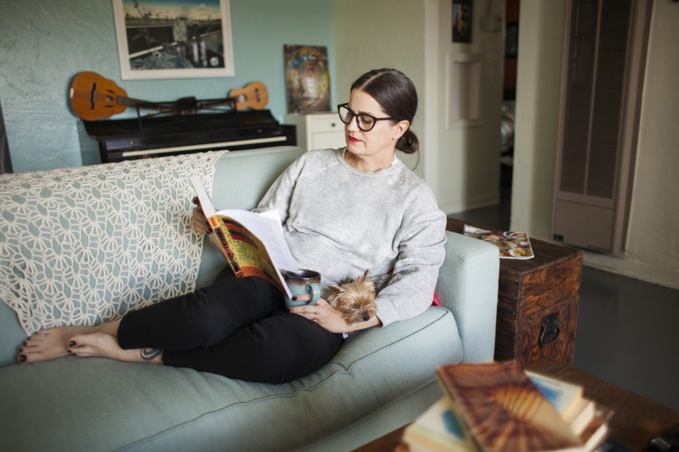 A woman curled up on a blue sofa in her creative home reading a book with her small dog in her lap.